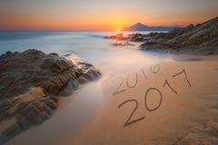 Dígitos 2016 y 2017 en la arena de la costa en la salida del sol Fotografía de archivo
