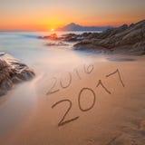 Dígitos 2016 y 2017 en la arena de la costa en la salida del sol hermosa Foto de archivo