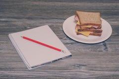 Dîner au travail Sandwich avec du jambon et la saucisse d'un plat blanc, carnet avec pencile là-dessus Vue horizontale, backgrou  Photographie stock libre de droits