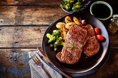 Dîner de bifteck, de pomme de terre et de légume sur la table Photo stock