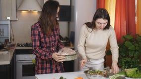 Dîner de cuisinière d'amie de deux filles ensemble Les filles emballent le poulet entier dans la douille pour faire dans cuire au banque de vidéos