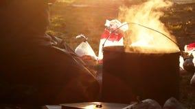 Dîner de cuisinier de randonneurs sur le feu banque de vidéos
