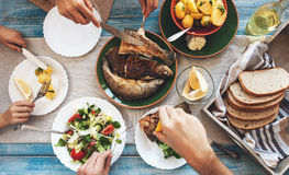 Dîner de famille avec les poissons, la pomme de terre et la salade frits image stock