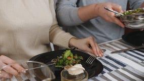 Dîner de famille Couples dînant ensemble dans la cuisine L'homme met la salade sur le plat à son épouse banque de vidéos