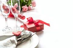 Dîner de jour de valentines avec le couvert de table avec le cadeau rouge, verre pour le champagne, ornements de coeur avec l'arg Photos libres de droits