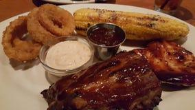 Dîner de nervures, de poulet et de maïs de barbecue avec des anneaux d'oignon Image stock