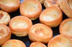 Dîner de Noël, puddings de Yorkshire faisant cuire au four dans le four Photo stock