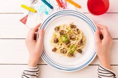 Dîner de repas dans des mains de l'enfant - spaghetti avec des champignons photographie stock