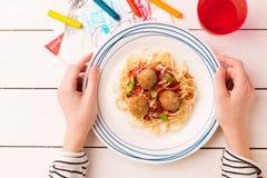 Dîner de repas dans des mains de l'enfant - spaghetti et boulettes de viande images libres de droits