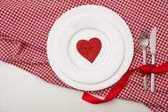 Dîner de valentines, coeur rouge des plats blancs, nappe à carreaux rouge, fond blanc photos stock