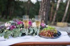 Dîner romantique dehors Verres avec le champagne, les raisins et beaucoup de fleurs sur le conseil en bois Photo stock