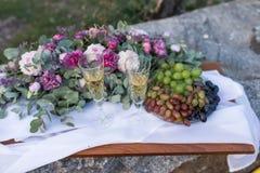 Dîner romantique dehors Verres avec le champagne, les raisins et beaucoup de fleurs sur le conseil en bois Images libres de droits