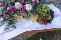 Dîner romantique dehors Verres avec le champagne, les raisins et beaucoup de fleurs sur le conseil en bois Image stock