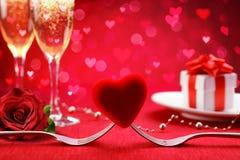 Dîner romantique - fourchettes et coeur avec le cadeau Defocused et la Champagne photographie stock