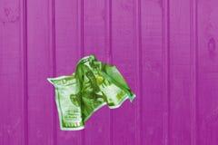 Dólar amarrotado contra uma textura de madeira do fundo cor-de-rosa imagem de stock