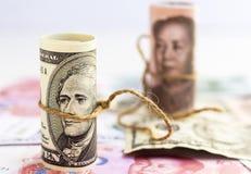 Dólar americano contra a cédula do yuan da porcelana em uma pilha da proibição das moedas Imagem de Stock Royalty Free