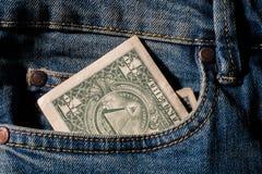 Dólar americano do dinheiro no texto do fundo da sarja de Nimes do bolso de calças de ganga foto de stock