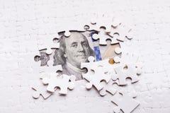 Dólar americano ocultado bajo pedazos del rompecabezas imagenes de archivo