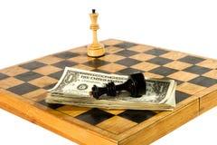 Dólar americano y figuras del ajedrez en un tablero de ajedrez fotografía de archivo