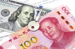 Dólar americano y nota china del yuan con una llave Imagen de archivo libre de regalías