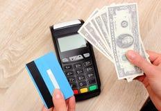 Dólar de las monedas con la tarjeta de crédito y terminal del pago en el fondo, concepto de las finanzas Imagen de archivo libre de regalías
