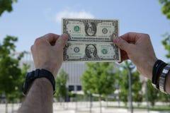 Dólar en las manos en la reflexión de espejo contra el cielo azul y el follaje verde foto de archivo