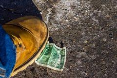 Dólar sob botas na terra Fotos de Stock Royalty Free