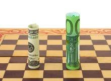 Dólar y euro en tarjeta de ajedrez fotografía de archivo