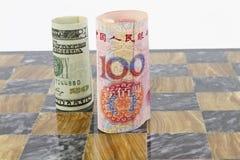 Dólar y Yuan en tarjeta de ajedrez Fotos de archivo