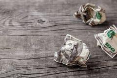 Dólares amarrotados em uma tabela de madeira velha fotografia de stock royalty free