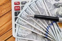Dólares americanos, calculadora y pluma fotografía de archivo libre de regalías