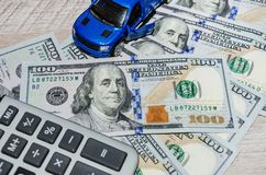 Dólares americanos da calculadora e um carro azul do brinquedo em uma tabela de madeira fotos de stock royalty free