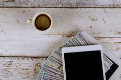D?lares americanos de dinero y taza digital de la tableta y de caf? de la tecnolog?a en la tabla de madera fotos de archivo