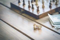 Dólares americanos e figuras da xadrez em um de madeira velho Fotos de Stock