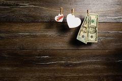 Dólares americanos en dos billetes de banco y corazones para la venta grande que cuelga con las pinzas Venta del día de fiesta imagen de archivo