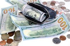 Dólares americanos na bolsa preta e moedas em um fundo branco Fotos de Stock Royalty Free