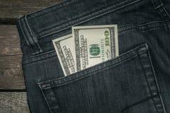 Dólares americanos no bolso das calças de brim Foto de Stock Royalty Free