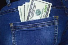 Dólares americanos no bolso traseiro das calças de brim imagem de stock