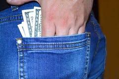 Dólares americanos no bolso traseiro das calças de brim imagens de stock royalty free