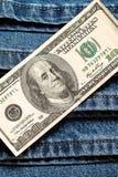 100 dólares americanos no fundo das calças de brim Fotos de Stock