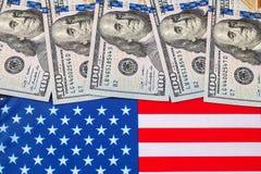 Dólares americanos sobre la bandera de los Estados Unidos Imagen de archivo