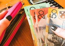 D?lares australianos del dinero, con el cuaderno y la calculadora en la tabla Conceptos financieros y de la inversi?n imagenes de archivo