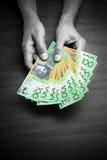 Dólares australianos do dinheiro das mãos fotografia de stock