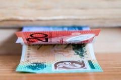 Dólares australianos 20, 100 notas del dólar y cuentas al lado de los libros en el foco selectivo $ Fotos de archivo libres de regalías