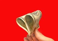 Dólares bajo la forma de corazón en un fondo rojo. Fotografía de archivo