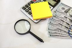 Dólares, calculadora e lente de aumento e folha de papel amarela para a inscrição imagens de stock