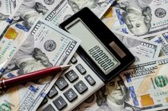Dólares, calculadora e pena fotografia de stock royalty free