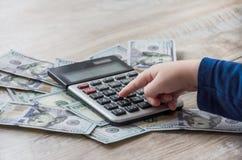 Dólares, calculadora y mano en una tabla de madera fotos de archivo