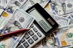 Dólares, calculadora y pluma fotografía de archivo libre de regalías
