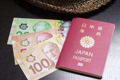 Dólares canadenses e passaporte japonês Imagens de Stock